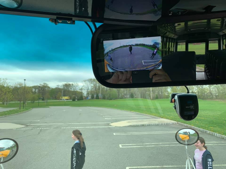 Bus drivers view of rear view mirror and kids in front of bus.