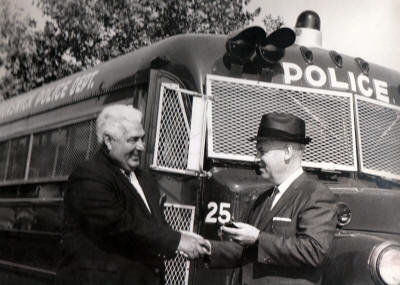 Vintage photo of Mr. Raphael shaking hands with another man in front of a police bus.