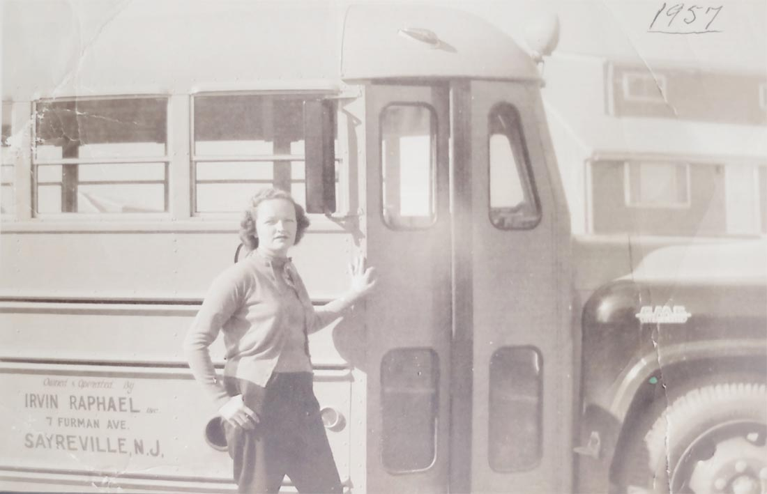 Vintage photo of young woman in front of bus door dated 1957.