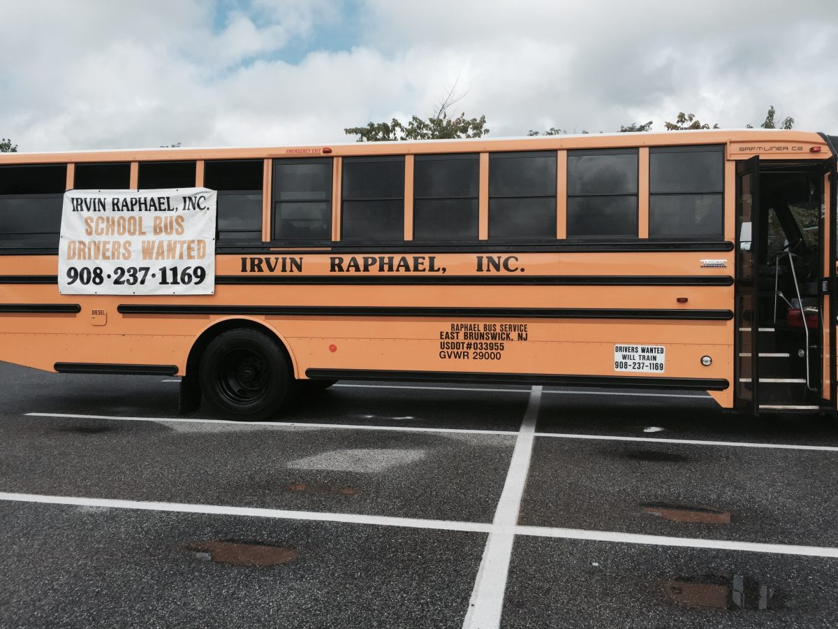 School bus in a parking lot with a large Bus Drivers Wanted sign on the side.